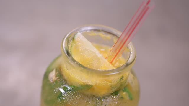 vídeos de stock e filmes b-roll de the yellow color of the mojito cocktail with lime - bebida fresca