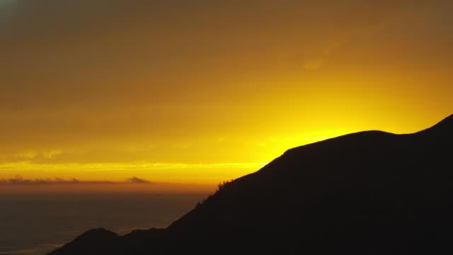 the yellow sky glows behind a rocky coastline. - küstenlandschaft stock-videos und b-roll-filmmaterial