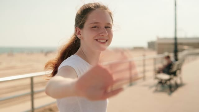 vídeos de stock e filmes b-roll de the young 18-years-old cheerful happy long-haired girl walking on the promenade at the brighton beach waterfront - 18 19 years