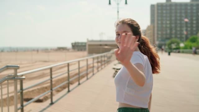 stockvideo's en b-roll-footage met 18-jaar oude vrolijk gelukkig langhaar meisje lopen op de promenade in het brighton beach waterfront - 18 19 years