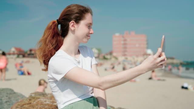 stockvideo's en b-roll-footage met 18-jaar-oud meisje maken een selfie met haar smartphone bij brighton beach - 18 19 years