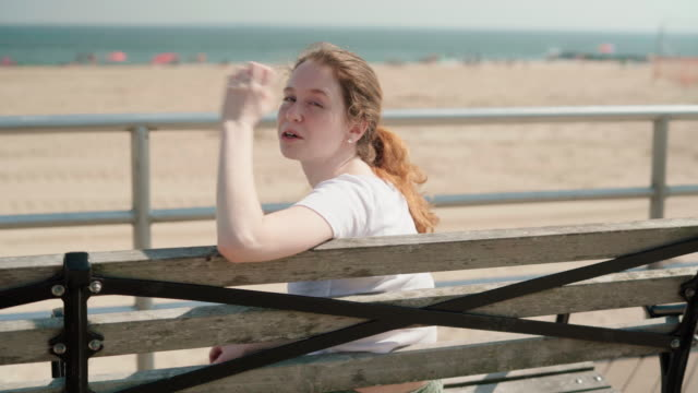 the young 18-years-old girl resting sitting on the bench at the promenade - long island video stock e b–roll