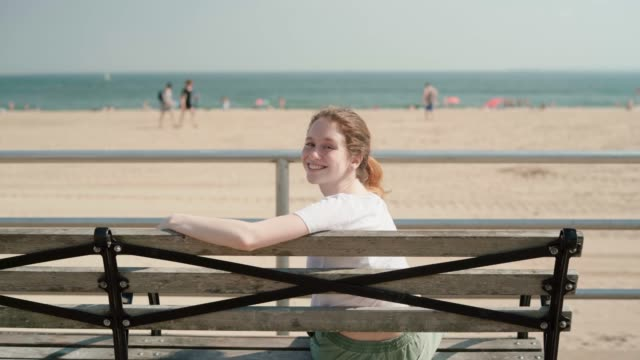 The young 18-years-old girl resting sitting on the bench at the promenade