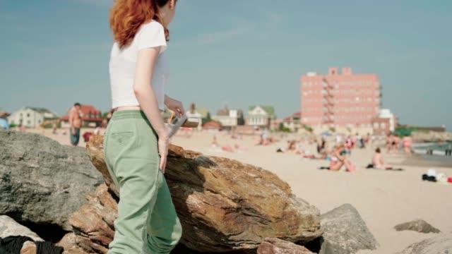 stockvideo's en b-roll-footage met 18-jaar-oud meisje zittend op de rotsen en schoonmaken van haar voeten uit zand na de wandeling op het strand van brighton - 18 19 years