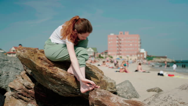 vídeos de stock e filmes b-roll de the young 18-years-old girl sitting on the rocks and cleaning her feets from sand after walk on the brighton beach - 18 19 years