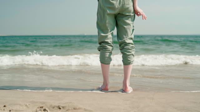 stockvideo's en b-roll-footage met 18-jaar-oud meisje permanent aan de rand van het water aan het strand van brighton - 18 19 years