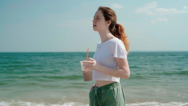 stockvideo's en b-roll-footage met 18-jaar-oud meisje lopen en het drinken van een milkshake in brighton beach - 18 19 years