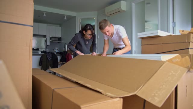 the young 30 years old man and teenager girl unboxing and assembling furniture in the new apartment - box container stock videos and b-roll footage