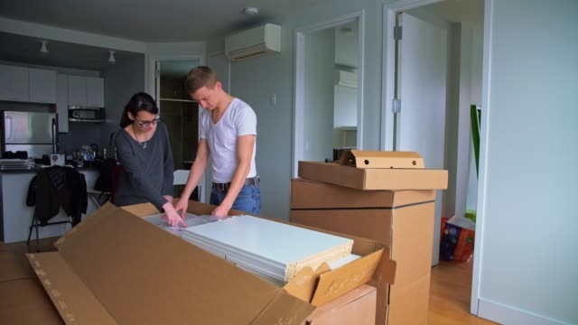 vídeos de stock e filmes b-roll de the young 30 years old man and teenager girl unboxing and assembling furniture in the new apartment - 30 34 years