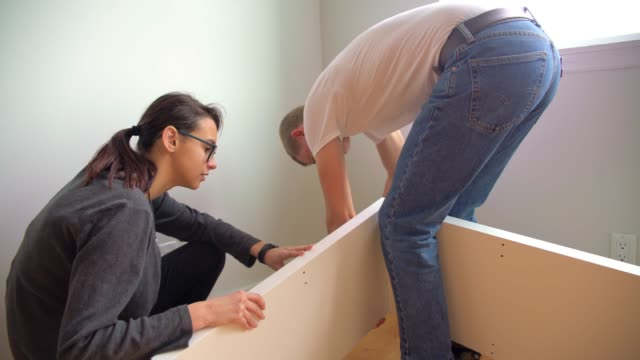 the young 30 years old man and teenager girl unboxing and assembling furniture in the new apartment - 25 29 years stock videos and b-roll footage