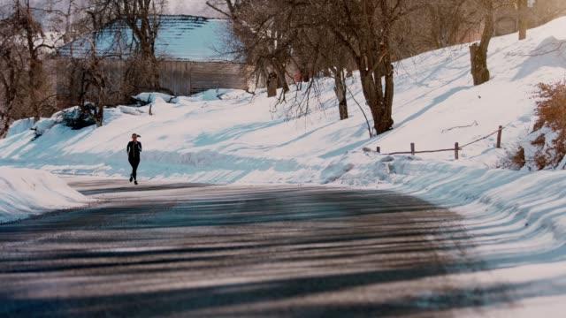 la giovane donna atletica che corre su una strada di montagna durante le soleggiate giornate invernali. - video stock - sunny video stock e b–roll