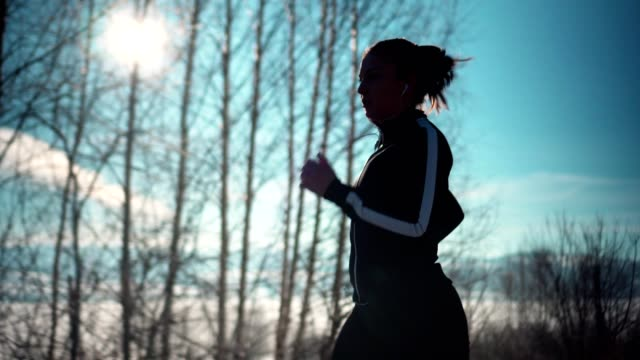 The Young athletic woman running on a Mountain road during sunny winter days. - Stock video
