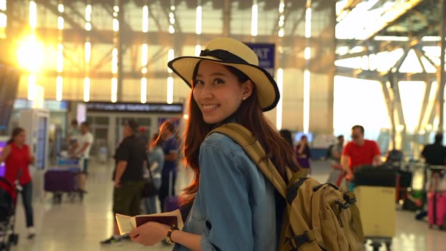 the young casual woman in travel casual smiling with the camera in the terminal airport.air travel concept. - young women stock videos & royalty-free footage