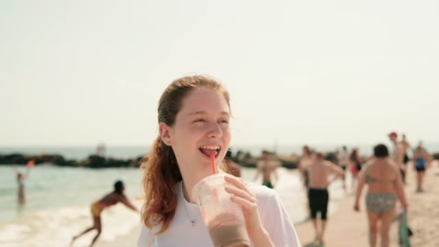 vídeos de stock e filmes b-roll de the young cheerful 18-years-old girl drinking a milkshake, waving and resting brighton beach - 18 19 years