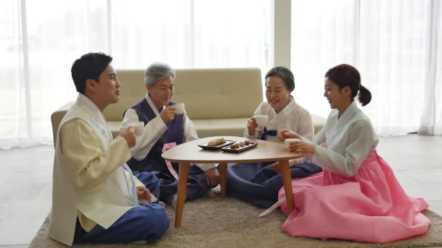 vídeos de stock e filmes b-roll de the young couple in korean dress talk with their parents on new year's day - korean new year