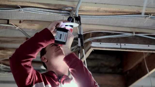 the young electrician installs the electric lamp on the ceiling. - electrician stock videos & royalty-free footage