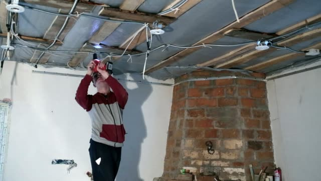 the young electrician installs the electric lamp on the ceiling. - electrician stock videos and b-roll footage
