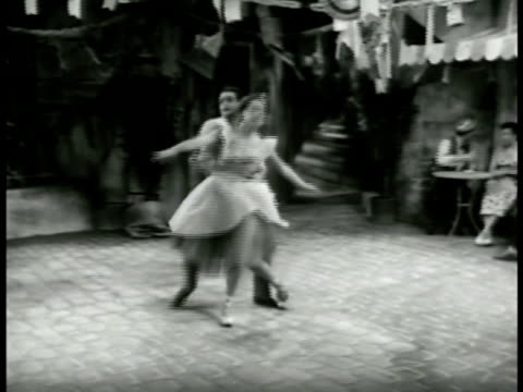 vidéos et rushes de the young lovers meet downstairs dance ballet together alone in the square pas de deux both then sitting at a cafe table cuddling in each others arms - 1952