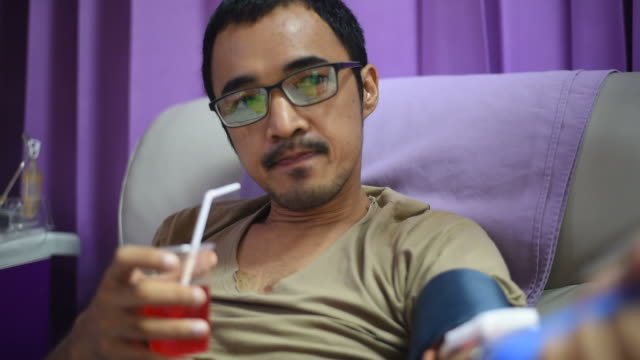 the young man drinking calcium water and squeezes the ball in his hand during single donor platelets blood at the hospital. - blood donation stock videos and b-roll footage
