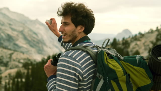 the young man, hipster, tourist - hiker and backpacker, filming the yosemite from the  olmsted point with the action camera - looking around stock videos and b-roll footage