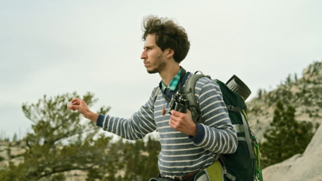 The young man, hipster, tourist - hiker and backpacker, filming the Yosemite from the  Olmsted Point with the action camera