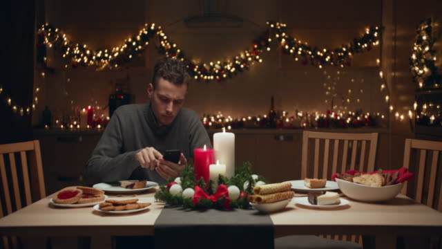 vídeos de stock e filmes b-roll de the young man is waiting for friends for a christmas party at home. none of his friends came to the christmas party. he blows out the candles sadly and alone. - loneliness