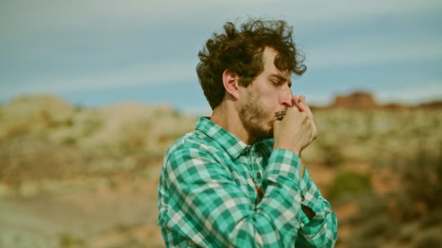 The young man playing mouth organ in the desert