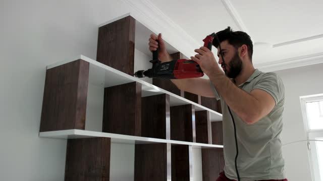 vidéos et rushes de le jeune homme tente lui-même de plier sa bibliothèque. - installer