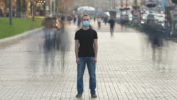 The young man with face mask stands in the crowded street. time lapse