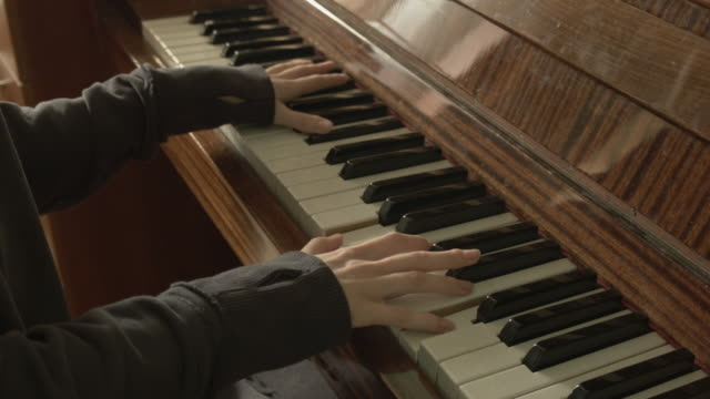 den unga kvinnan spelar entusiastiskt och passionerat vintage piano. - människofinger bildbanksvideor och videomaterial från bakom kulisserna