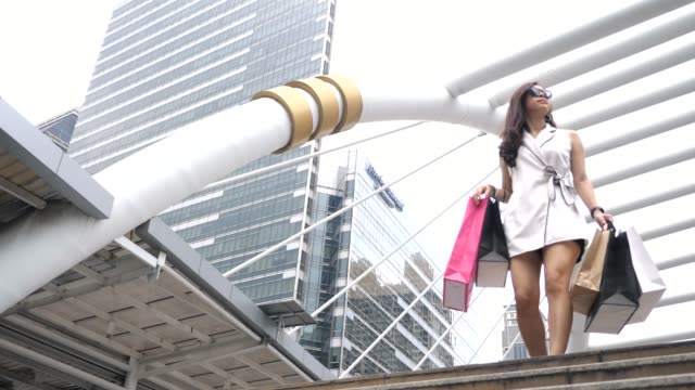 the young woman walks with shopping bags - shopaholic stock videos & royalty-free footage