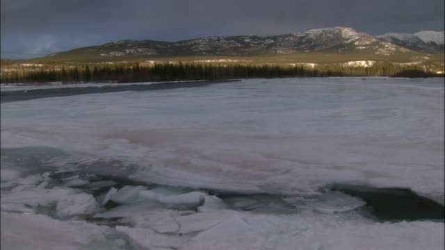the yukon's tagish lake thaws with seams of water running between a layer  of ice. - whitehorse stock videos and b-roll footage