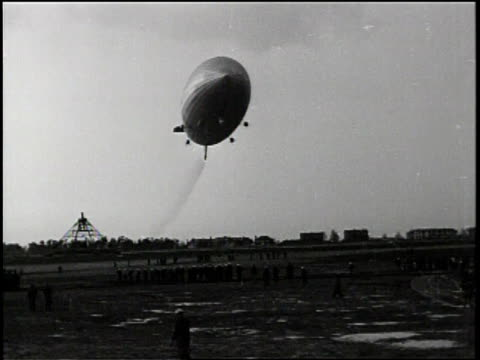 the zeppelin flies low over a field / people gather and watch / - newsreel stock videos & royalty-free footage