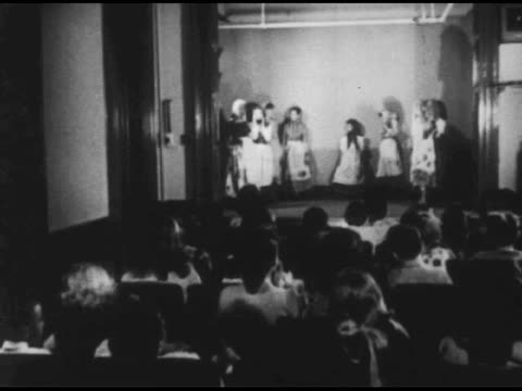 / theater audience of children clapping / shot of bowing stage play actors / children gathered at museum displays / young boys watch model train set.... - anno 1951 video stock e b–roll