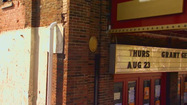 vídeos y material grabado en eventos de stock de theater building exterior tilt down to boy with bike, jib shot, 1950s period style - jib shot