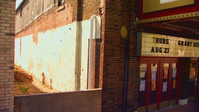 vídeos y material grabado en eventos de stock de theater building exterior tilt down to boy with bike zoom in, jib shot, 1950s period style - jib shot