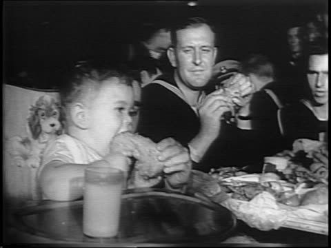 theater marquee touts american legion chicken dinner / montage of fried chicken piled onto table sorted served eaten by servicemen and women children - eaten stock videos & royalty-free footage