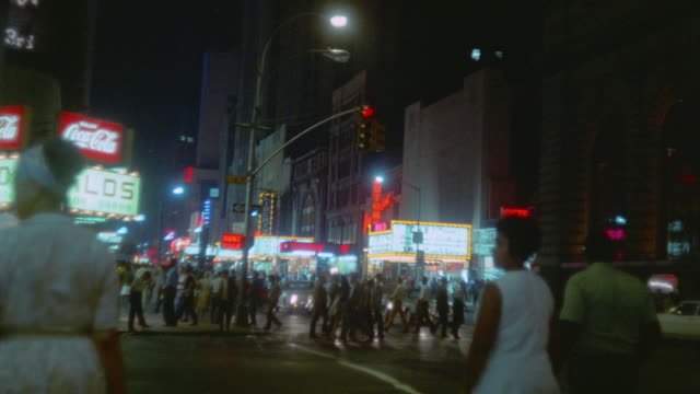 1969 ws montage theater marquees and crowds along 42nd street at 8th avenue at night / new york city - anno 1969 video stock e b–roll