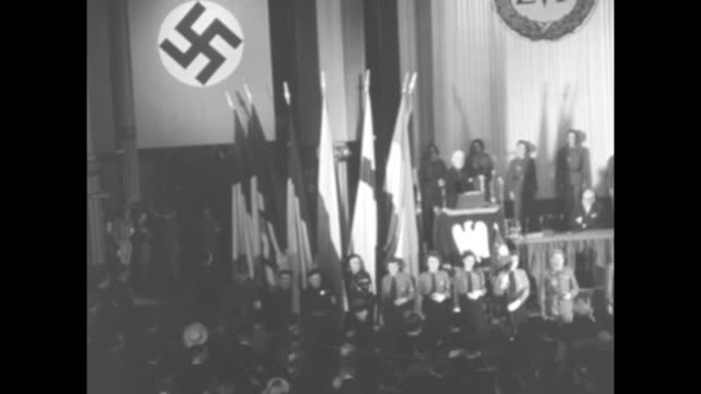 Theatre or large hall with Nazi officials on stage large swastika flags on sides and backdrop with LVF on it other flags standing to sides / stage...