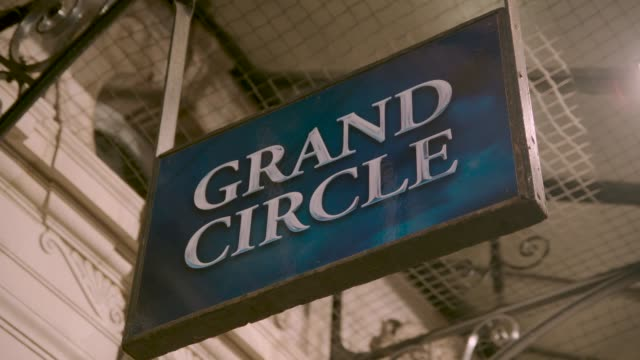 theatre sign reading 'grand circle' sways in wind - ウェストエンド点の映像素材/bロール
