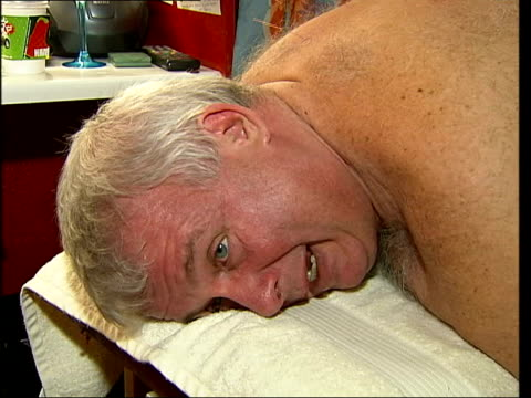 theatre therapy trainer practicing acupunture on christopher biggins back christopher biggins interviewed as undergoes treatment sot describes reason... - symptom stock videos and b-roll footage