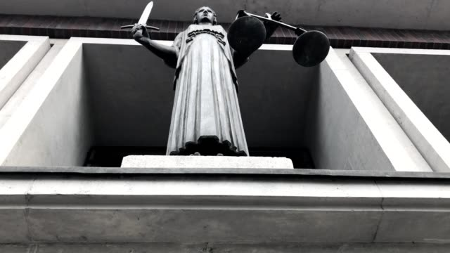themis with scale and sword in court - palazzo di giustizia video stock e b–roll