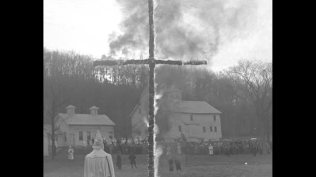 vídeos de stock, filmes e b-roll de cu then ws of burning cross in field at daytime rally / few seconds of old rugged cross / [note exact month/day not known] - ku klux klan