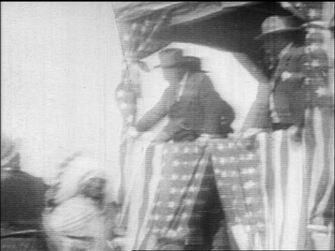 Theodore Roosevelt on platform shaking hands with Native Americans / documentary