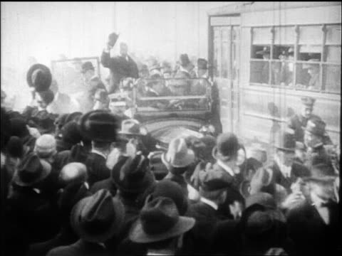 Theodore Roosevelt riding in car holding up hat past crowd / documentary