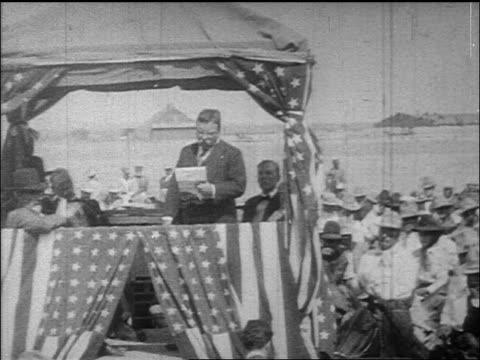 Theodore Roosevelt speaking on platform adorned with US flags / documentary