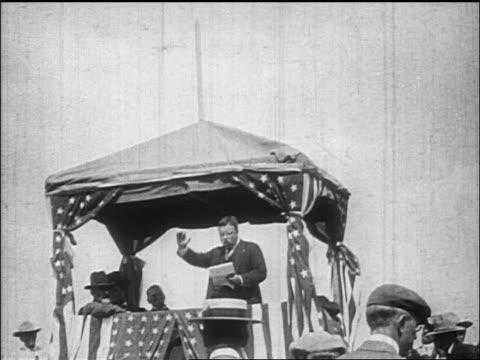 Theodore Roosevelt speaking on platform with US flags hitting hand on podium / documentary
