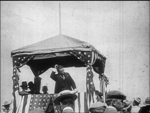 Theodore Roosevelt speaking on platform with US flags shaking fist / documentary