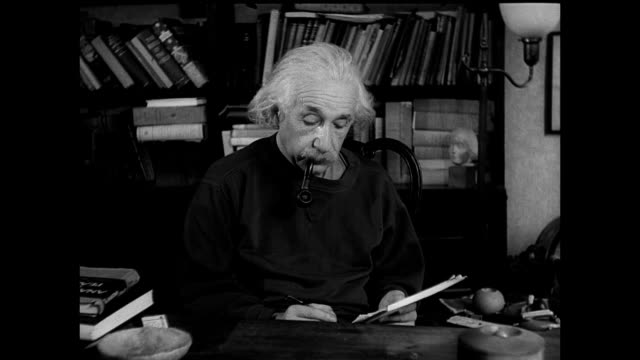 RELATIVITY Theoretical Physicist Albert Einstein working at desk looking down smoking pipe books BG CU Paper on desk w/ three parts of physics...