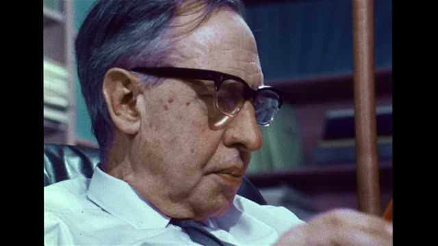 Theoretical physicist George Uhlenbeck sitting in office reading book taking off glasses thinking PHOTOGRAPHS Space nebulae star clusters [VO SOT...